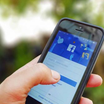 Close up of mobile phone showing Facebook search ads