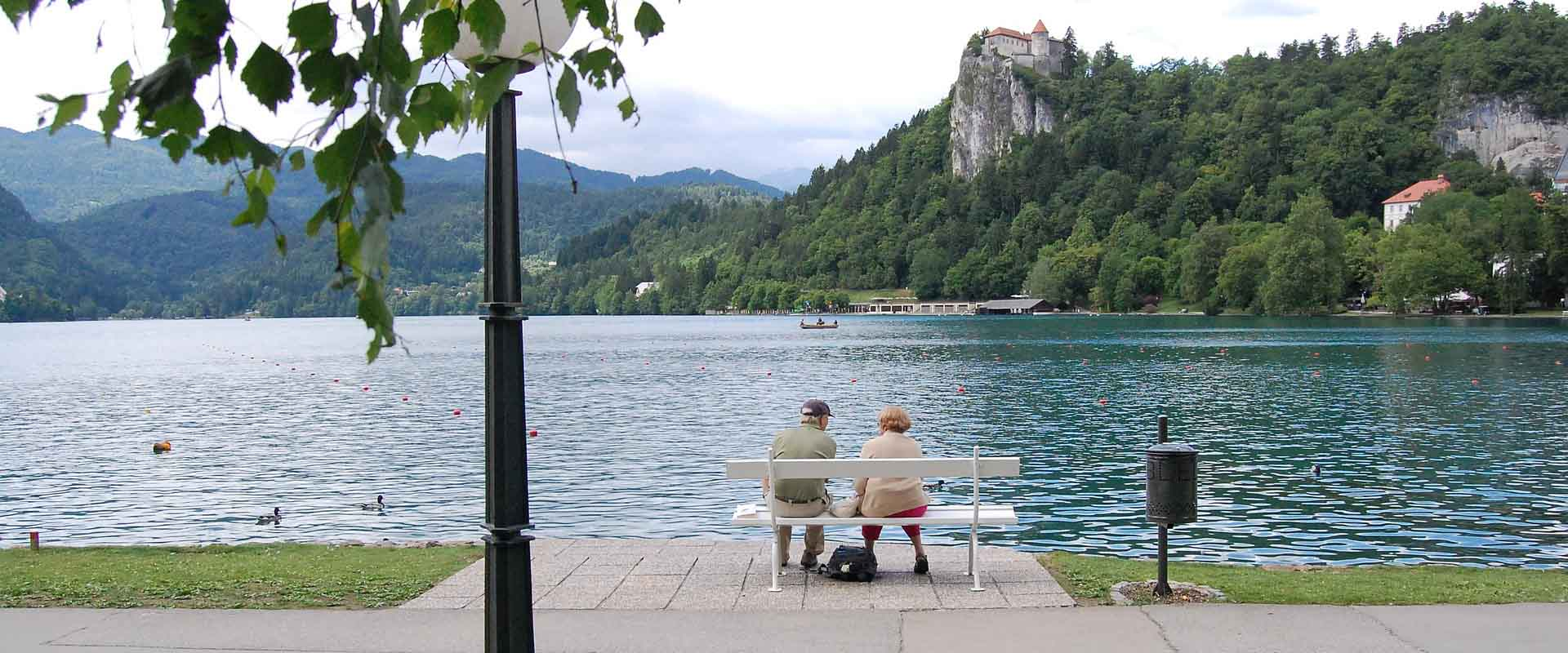 Couple on a bench overlooking a river with mountains