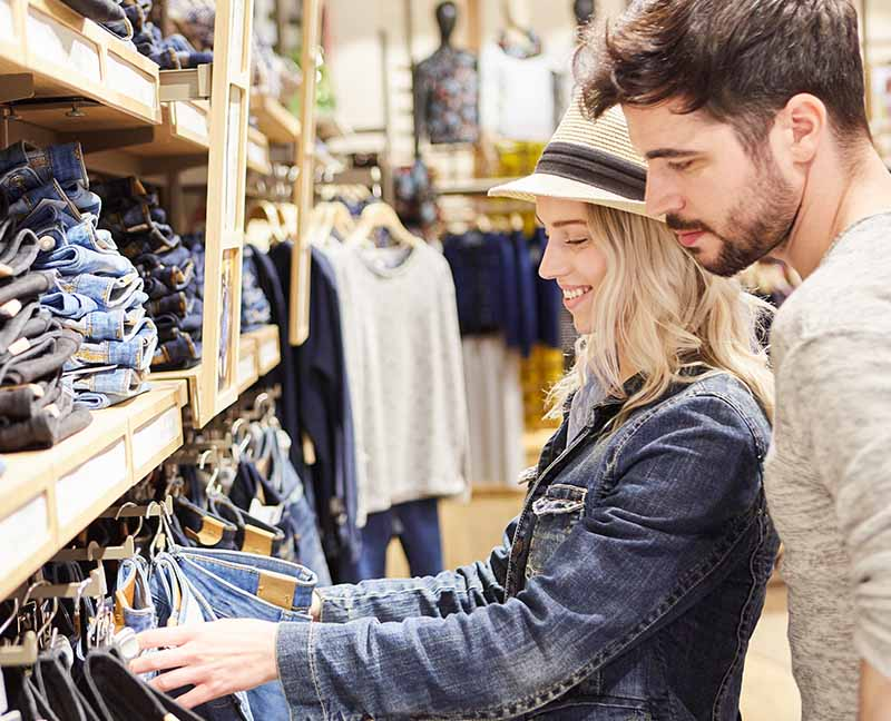 A couple looking at jeans in a shop